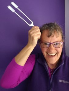 Dianne Ashcroft with a tuning fork held to her head